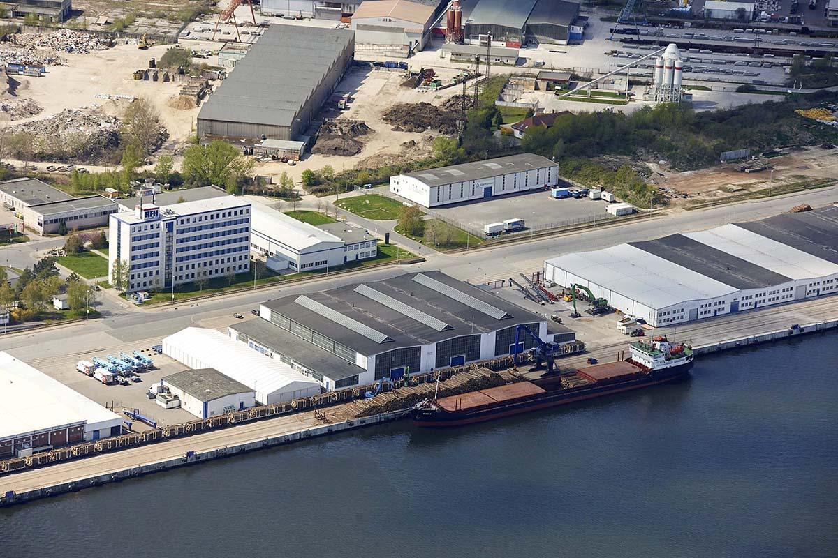Blick von oben auf einen Frachter, Holzstämme und Hallen des Fracht- und Fischereihafens Rostock