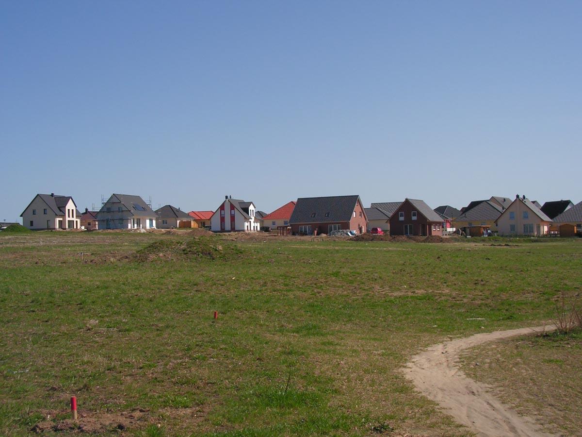 Wohngebiet mit grüner Wiese im Vordergrund