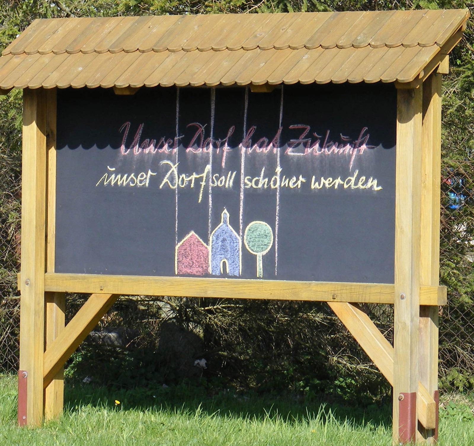 Tafel mit Schriftzug: Unser Dorf hat Zukunft - unser Dorf soll schöner werden