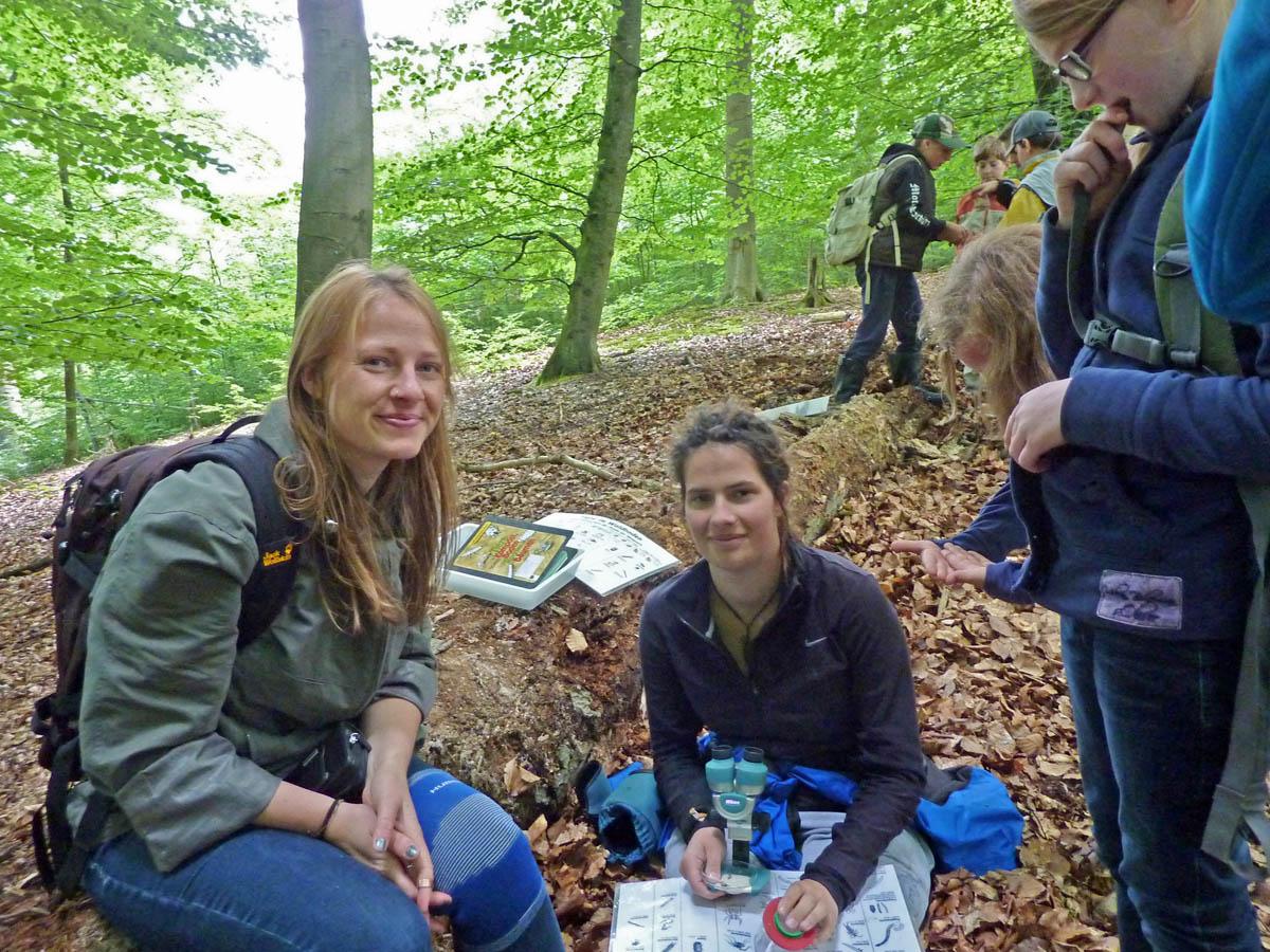 FÖJlerin Louise Globig (Mitte) erkundet mit Schülern Tiere des Waldbodens<p>© Claus Weber</p>